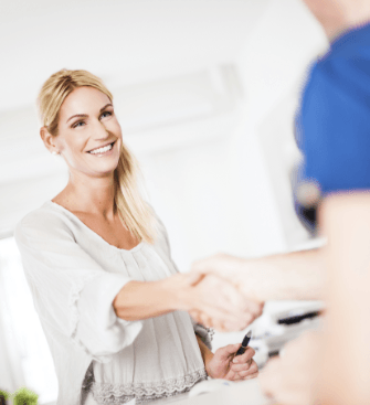 Woman shaking hands with oral surgery team member after dental implant visit