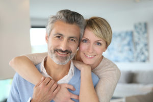Smiling middle-aged couple after dental implant surgery